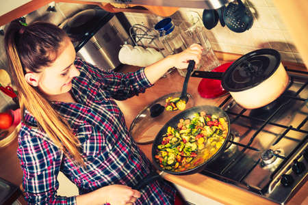 meal: Woman in kitchen cooking stir fry frozen vegetables. Girl frying making delicious dinner food meal.