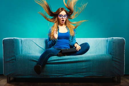 Technology internet concept. Fashion woman wearing denim sitting with tablet on couch hair blowing face expression blue color Foto de archivo
