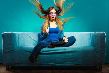 sorprendido: Concepto de internet Tecnología. Moda mujer llevaba denim se sienta en el sofá con la tableta pelo soplando azul color expresión de la cara Foto de archivo