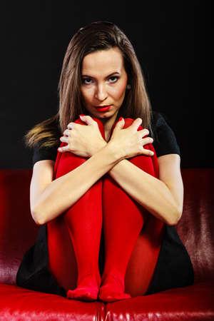 pantimedias: Mujer triste vívida pantimedias de color sentado en el sofá negro