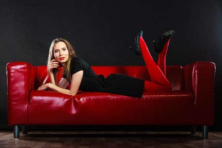 medias veladas: Equipo de la manera elegante. Piernas largas mujer de moda en rojo vivo pantimedias de colores relajantes en el sofá de interior en negro Foto de archivo