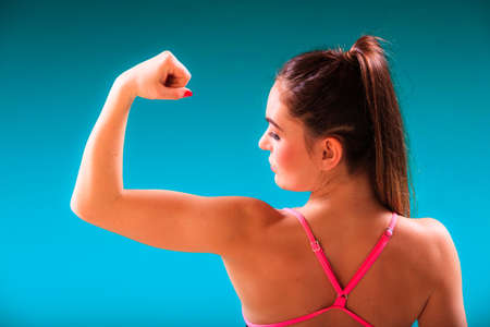 active lifestyle: Sport active lifestyle. Sporty woman female swimmer fit body in swimsuit showing her muscles biceps blue water background Stock Photo