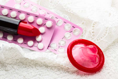 Healthcare medicine, contraception and birth control. Closeup oral contraceptive pills, condom and red lipstick on lace lingerie.