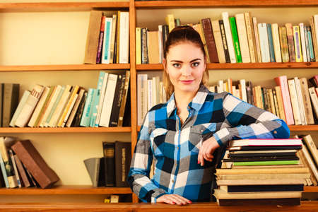 pile of books: Education school concept. Intelligent female student fashion girl plaid blue shirt in college library with pile books