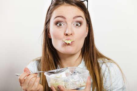 completo: Mujer con la boca llena de comer ensalada de verduras frescas. Niña feliz y alegre disfrutando de la comida sana. Nutrition.