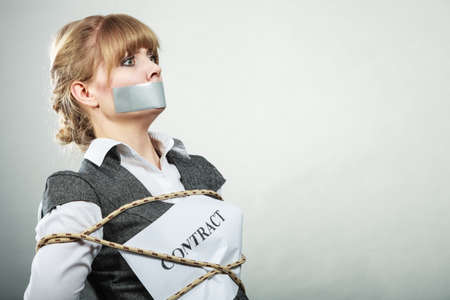 taped: Afraid businesswoman bound by contract terms and conditions with mouth taped shut. Scared woman tied to chair become slave. Business and law concept. Stock Photo