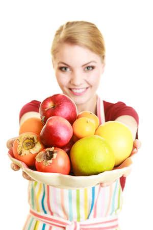 nutricion: La dieta y la nutrición. Ama de casa feliz o cocinero en el delantal de cocina a rayas ofreciendo aislado fruta sana