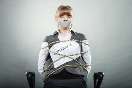 bondage: Afraid businesswoman bound by contract terms and conditions with mouth taped shut. Scared woman tied to chair become slave. Business and law concept. Stock Photo