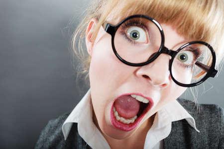 SECRETARIA: Bastante joven gritos secretario empresaria y gritando. Mujer trabajador de cuello blanco con gafas. Foto de archivo