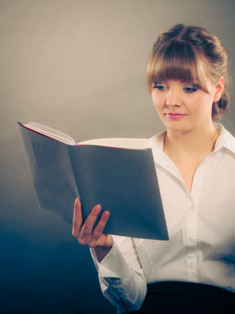well read: Woman reading and learning with book textbook. Education leisure. Young girl in white shirt studying for exam.