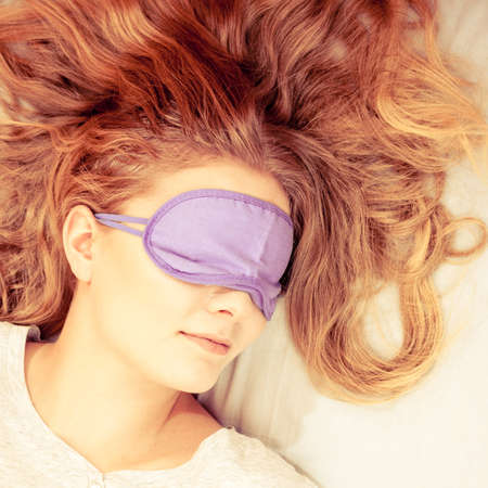 taking nap: Tired woman sleeping in bed wearing blindfold sleep mask. Young girl taking nap. Instagram filtered.