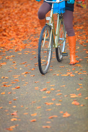 active: Active woman girl riding bike bicycle relaxing in fall autumn park. Healthy lifestyle and recreation leisure activity. Stock Photo