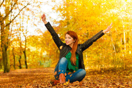 freedom park: Happiness freedom leisure concept. Redhair woman relaxing in autumn park throwing leaves up in the air. Beautiful girl in orange forest foliage outdoor. Stock Photo