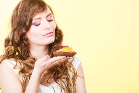 indulging: Bakery sweet food indulging and people concept. Cute attractive woman closed eyes holds cake cupcake in hand smelling yellow  Stock Photo