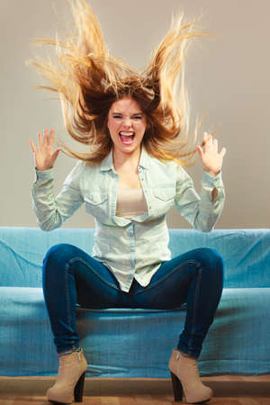 hair wind: Young people happiness concept. Fashionable girl wearing denim relaxing on blue couch wind in hair face expression Stock Photo