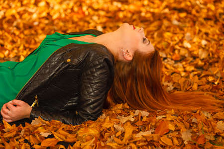 lying on leaves: Ecology earth, eco friendly and love nature concept. Portrait young redhaired woman lying in autumn orange leaves.
