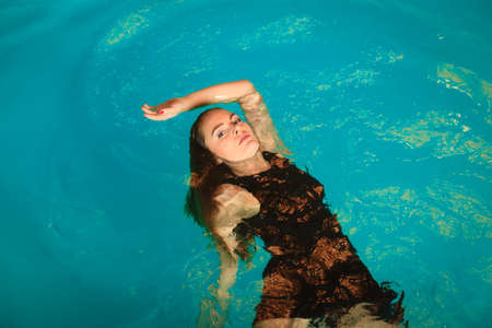 floating on water: Woman relaxing at swimming pool. Young girl floating. Water aerobics fitness.