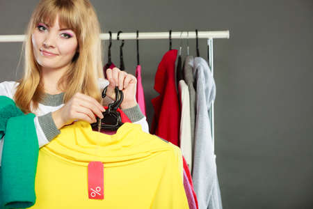 price label: Good shopping sale concept. Blonde fashionable woman choosing clothes holding discount red label with percent sign in hand