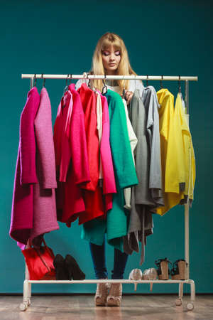Pretty woman choosing clothes to wear in wardrobe. Attractive young girl customer shopping in mall shop. Fashion clothing sale concept. Foto de archivo