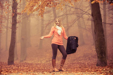confused guidance: Lost confused woman in foggy fall autumn park searching direction. Fashion young girl holding jacket. Female looking for guidance in forest.