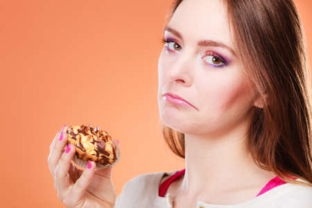 unhappy people: Diet dilemma, grow fat from eating sweets concept. Sad unhappy woman holds cake cupcake in hand orange background