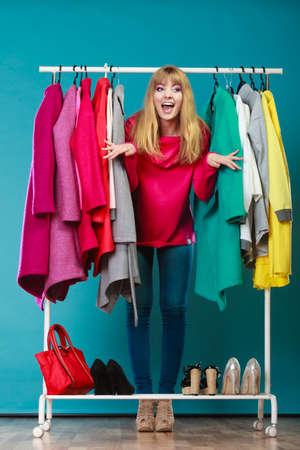 gorgeous girl: Happy smiling pretty woman choosing clothes to wear in wardrobe. Gorgeous young girl customer shopping in mall shop. Fashion clothing sale concept. Stock Photo
