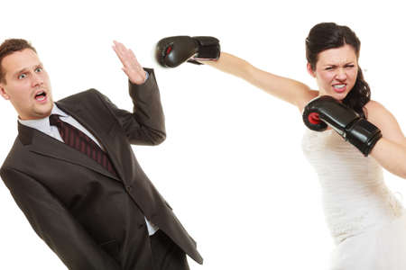 beaten: Bad relationship conflict. Married couple fighting. Wife showing her husband whos boss. Angry woman bride in wedding dress boxing punching man groom isolated on white