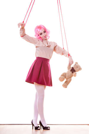 bondage girl: Mental disorder concept. Young woman girl stylized like marionette puppet on string with teddy bear toy isolated on white background