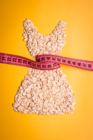 waist down: Dieting healthy eating slim down concept. Female dress shape made from oatmeal with measuring tape around thin waist on yellow