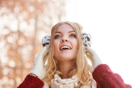 earmuff: Winter or autumn fashion ear protection. Portrait of lovely girl in warm clothes. Happy girl in earmuffs walking in foggy day autumnal park, outdoors Stock Photo