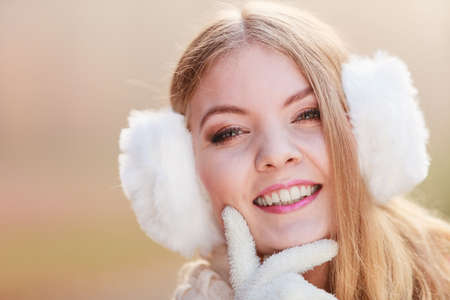 muff: Winter or autumn fashion ear protection. Portrait of lovely girl in warm clothes. Happy girl in earmuffs walking in foggy day autumnal park, outdoors Stock Photo
