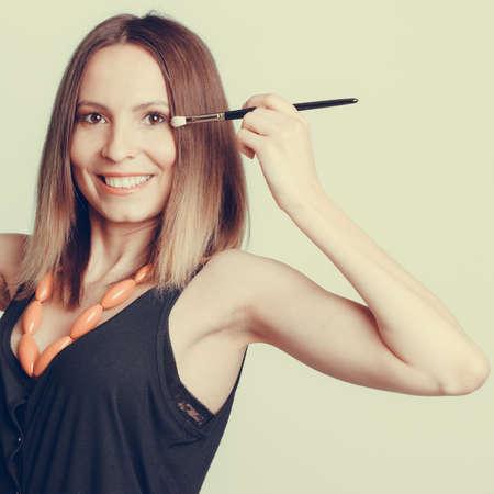 and eyelid: Woman stylist applying eye shadow professional makeup brush. Girl beautifying eye eyelid. Make up makeover concept.