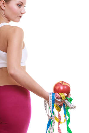 measures: Young woman girl holding apple and tape measures. Slimming and dieting. Healthy lifestyle nutrition concept. Rear back view. Isolated on white.