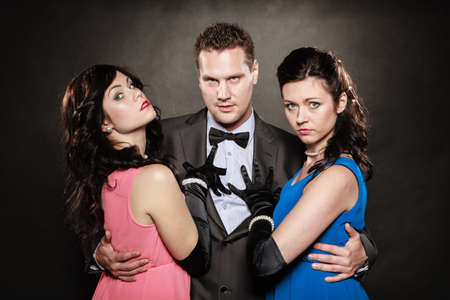 threesome: Elegant people preparing for night out. Man in suit holding two elegant women waist. Black grey background. Studio shot.