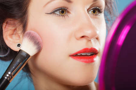 cheekbones: Cosmetic beauty procedures and makeover concept. Closeup woman applying makeup blusher with brush looking into mirror. Girl gets blush on cheekbones, on blue Stock Photo