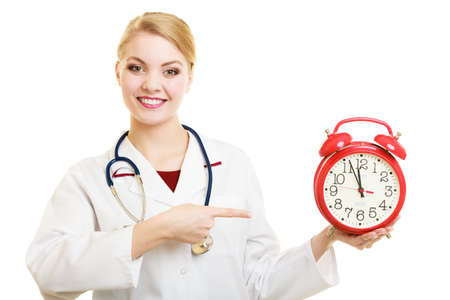 reminding: Health care medical checkup concept. Doctor with big red alarm clock reminding to do health check isolated on white