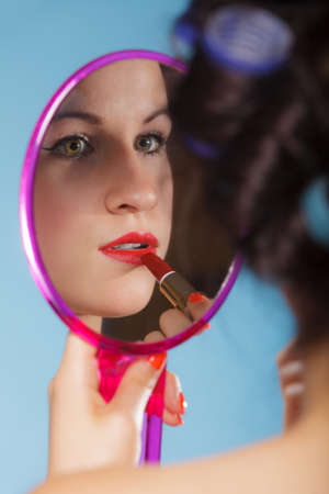 young woman preparing to party, getting ready for going out. Girl styling hair with curlers applying make up red lipstick looking at mirror retro style blue background