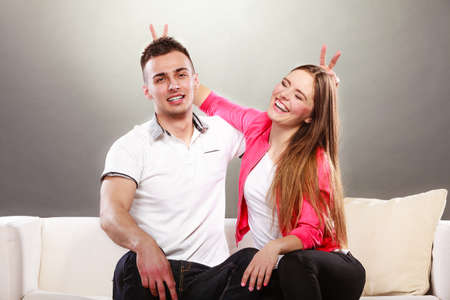 good boy: Happy couple having fun and fooling around. Joyful man and woman have nice time using fingers as bunny ears. Good relationship.