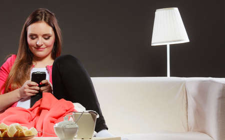 mobile internet: Woman using mobile phone texting and sending messages. Girl use new technology surfing internet sitting on couch at home. Stock Photo