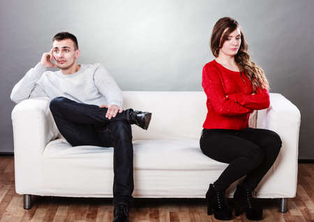 impasse: Bad relationship concept. Man and woman in disagreement. Young couple after quarrel sitting on sofa