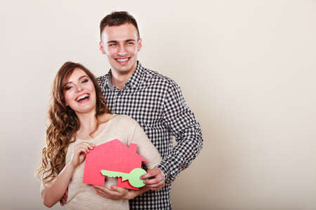 housing loan: Smiling young couple holding paper house and key. Husband and wife dreaming about new home. Housing and real estate concept.