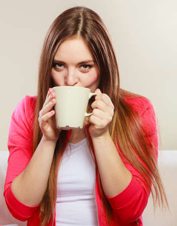 energizing: Woman drinking cup of coffee. Young girl with hot energizing beverage that keeps her awake. Energy and caffeine. Stock Photo
