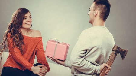 Sneaky insincere man holding axe giving gift present box to woman. Husband concealing hiding his true feelings from happy trusting wife. Untrue false intention. Relationship problems.   Stock Photo