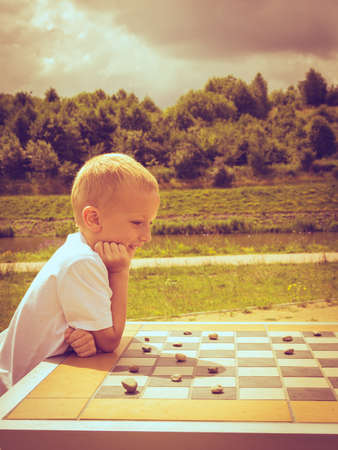 draughts: Draughts board game. Little boy clever child kid playing checkers thinking, outdoor in the park side view. Childhood and development