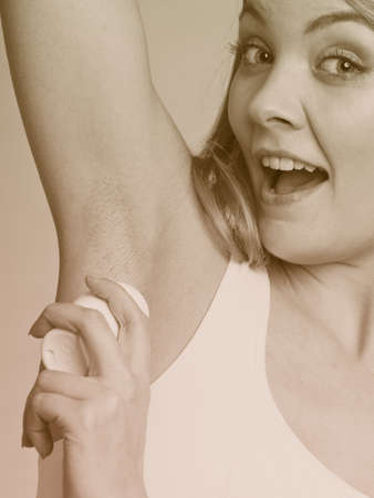 underarms: Daily skin care and hygiene. Girl applying deodorant stick in the armpit. Young woman putting antiperspirant in underarms sepia tone