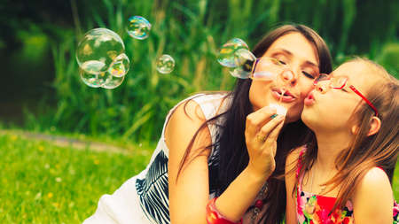 mother child: Mother and little girl daughter child blowing soap bubbles outdoor. Parent and kid having fun in park. Happy and carefree childhood. Good family relations.