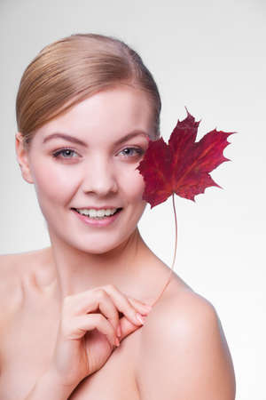 capillary: Skincare habits. Portrait of young woman with leaf as symbol of red capillary skin on gray. Face of girl taking care of her dry complexion. Studio shot.