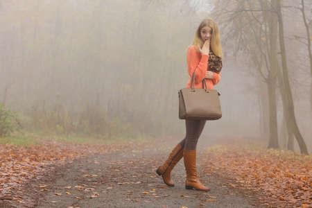 mujeres morenas: La moda de otoño. Mujer chica de moda el uso de ropa viva la celebración de un bolso del bolso de cuero marrón en la mano, caminando en el Parque de niebla otoñal, al aire libre Foto de archivo