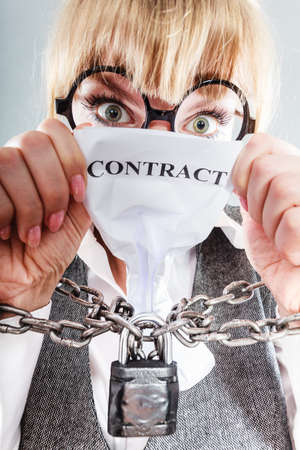 slave labor: Business and stress concept. Terrified businesswoman in glasses with chained hands holding contract grunge background unusual angle view Stock Photo