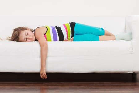 perezoso: Cansado agotado ni�a perezoso acostado en el sof� en casa. Ni�o so�oliento reclinaci�n relaja en el sof�. Foto de archivo